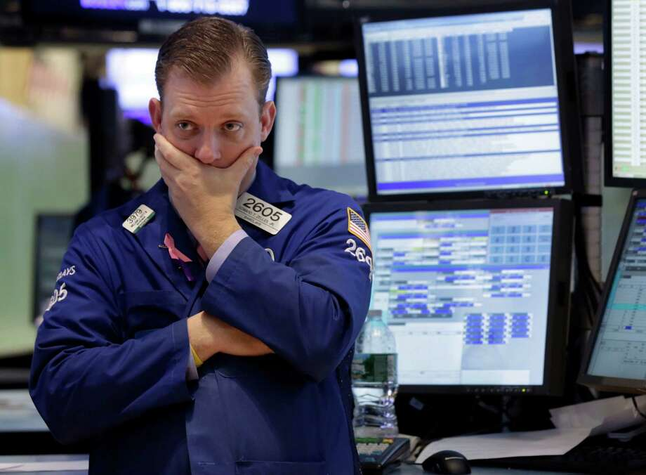 In this Thursday, Jan. 10, 2013, photo, specialist Edward Zelles works on the floor of the New York Stock Exchange. Wall Street futures were mostly flat in world markets prior to the opening bell Friday Jan. 11, 2013. (AP Photo/Richard Drew) Photo: Richard Drew