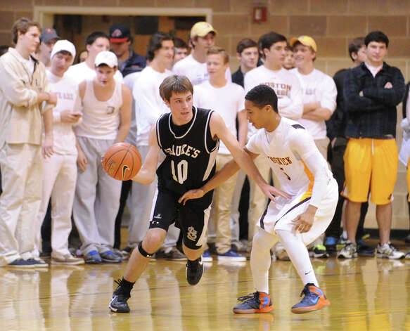 At left, Sean Callahan # 10 of St. Luke's dribbles while being covered by Henry Taylor of Brunswick during boys high school basketball game between Brunswick School and St. Luke's at Brunswick in Greenwich, Friday night, Jan., 11, 2013. Photo: Bob Luckey / Greenwich Time