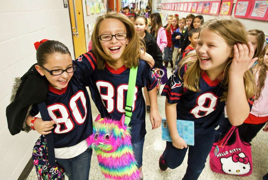 Christina Hardy, 8, left, walks to first class with her friends Abby Konvicka, 9, center, and Caroline Landrum, 9, Friday, Jan. 11, at Shadycrest Elementary in Pearland. Christina said she took her Texans jersey from her brother, Abby said her brother wore his JJ Watt jersey so she wore the Andre Johnson jersey, and Caroline had her own jersey. Pearland Independent School District superintendent  John Kelly, Ph. D., lifted the dress code to allow students to wear their Texans gear. Photo: Nick De La Torre, Houston Chronicle / © 2013  Houston Chronicle