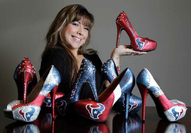 Christina Graham poses with her custom shoe designs Thursday, Jan. 10, 2013, in Houston. She also makes flats and other designs, but the Texans high heel style is in high demand.  Since October she has been so busy filling orders that she's not sure exactly how many she has created.  Depending on the design it takes from 2 to 4 days to make a pair. Photo: Melissa Phillip, Houston Chronicle / © 2013 Houston Chronicle