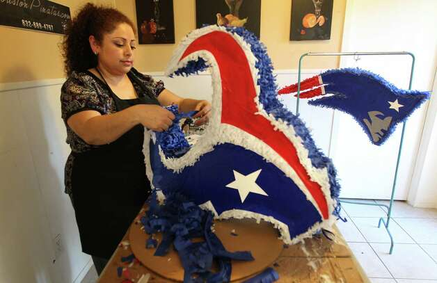 Maria Gonzalez, of Houston Pinatas, adds tissue paper while making a Houston Texans pinata which will be shipped to a customer in El Paso. Gonzalez makes pinatas for sports fans of opposing teams as well, such as the completed New England Patriots pinata that will given to local client. Gonzalez and her family will watch the game on Sunday afternoon, as they too are Texans fans. Photo: Mayra Beltran, Houston Chronicle / © 2013 Houston Chronicle