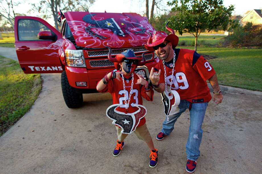 David Mendez with his son D.J., 10, are diehard  Texans fans and David drives a giant red truck with the Houston Texans logo on it. Photo: Karen Warren, Houston Chronicle / © 2013 Houston Chronicle