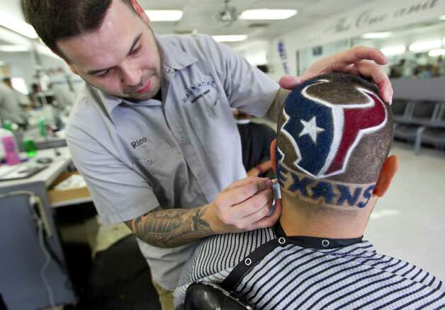 "Barber Chris ""Rico"" Ramirez works on putting color on a Texans logo into Carlos Flores' hair at Bad Boyz barber shop, Friday, Jan. 11, 2013, in Houston, in anticipation of the Texans playoff game against New England, this Sunday. Photo: Karen Warren, Houston Chronicle / © 2013 Houston Chronicle"