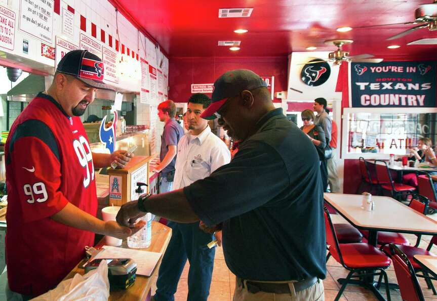 Co-owner of  Laredo Taqueria, Mario Celestino, left, serves customer Gilbert Bedford, right, Friday,