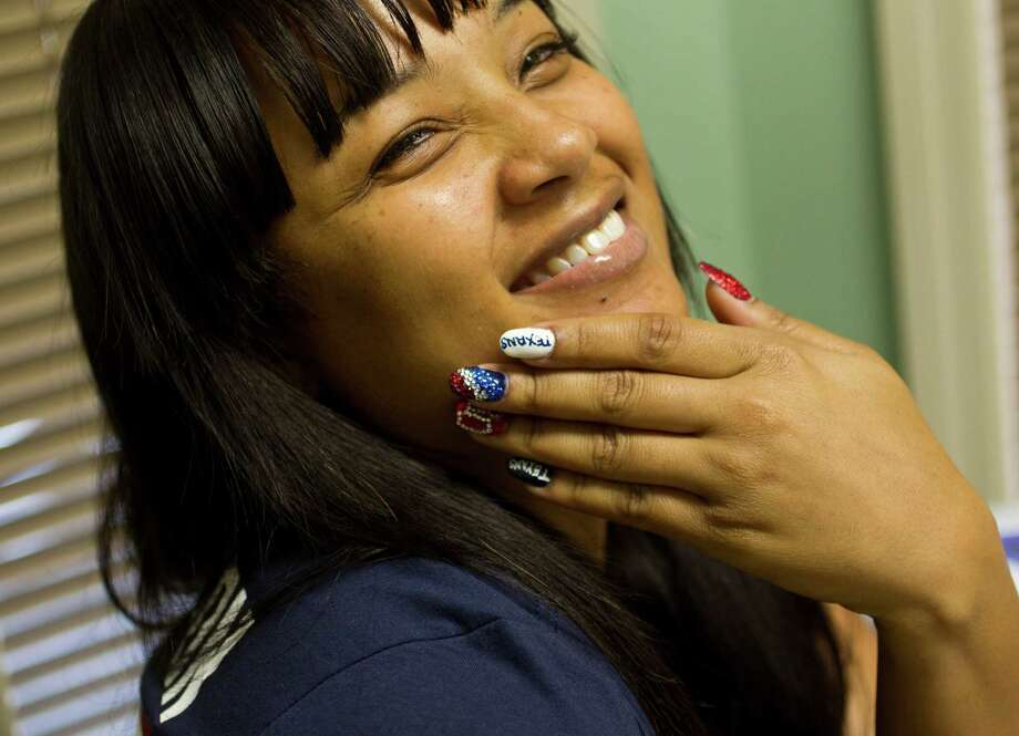 Virginia Griffin shows off her nails in Texans colors after getting them done by Johnnie Queen Minx, owner of Queen Minx Your Nail Palace, Friday, Jan. 11, 2013, in Houston, in anticipation of the Texans playoff game against New England, this Sunday. Photo: Karen Warren, Houston Chronicle / © 2013 Houston Chronicle