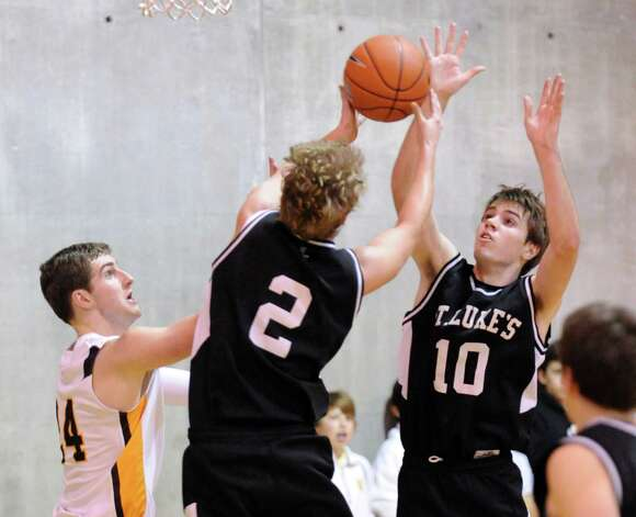 T.J. Simpson # 2 of St. Luke's grabs a rebound as teammate Sean Callahan, right, goes for the ball during boys high school basketball game between Brunswick School and St. Luke's at Brunswick in Greenwich, Friday night, Jan., 11, 2013. At left is Teddy Murphy # 24 of Brunswick. Photo: Bob Luckey / Greenwich Time