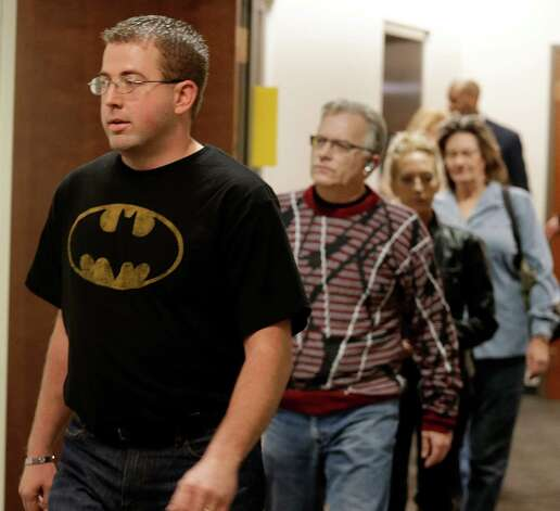 A man wears a Batman shirt as he arrives for court with other victims and family member for Aurora theater shooting suspect James Holmes at the courthouse in Centennial, Colo., on Friday, Jan. 11,  2013.  The judge granted a defense motion to delay the arraignment of Holmes until March 12. The decision comes a day after the judge ruled that Holmes should stand trial. (AP Photo/Ed Andrieski) Photo: Ed Andrieski