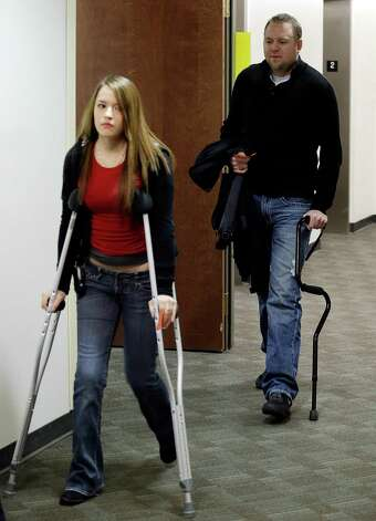Two people using crutches and a cane arrive for a court proceeding for Aurora theater shooting suspect James Holmes at the courthouse in Centennial, Colo., on Friday, Jan. 11,  2013. The judge granted a defense motion to delay the arraignment of Holmes until March 12. The decision comes a day after the judge ruled that Holmes should stand trial.  (AP Photo/Ed Andrieski) Photo: Ed Andrieski