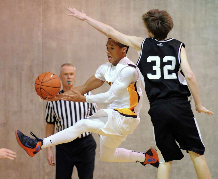 At left, Henry Taylor of Brunswick goes flying through the lane before passing while being defended by Walker Ross # 32 of St. Luke's during boys high school basketball game between Brunswick School and St. Luke's at Brunswicki n Greenwich, Friday night, Jan., 11, 2013. Photo: Bob Luckey / Greenwich Time