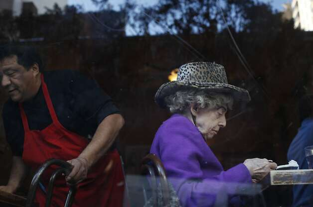 Marian B. Brown sits in the twins' usual window spot at Uncle Vito's pizza on Nob Hill. After her sister became ill, supporters pitched in to buy Marian her daily pizza. Photo: Mike Kepka, The Chronicle
