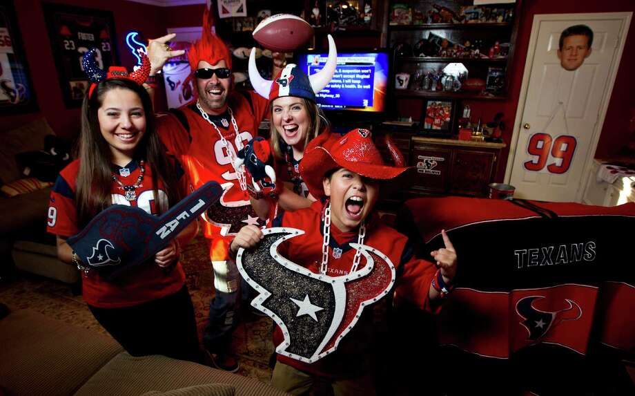 David Mendez and his wife, Nici, with daughter Madi, 13, and son D.J., 10, have decorated their den in Texans red, white and blue. All avid fans of the team, they jump into their swimming pool after every Texans score on game days. Photo: Karen Warren, Staff / © 2013 Houston Chronicle