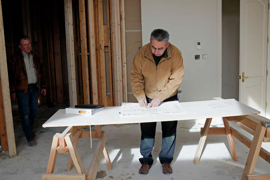 Designer Michael Cortez, right, and Vision Design and Build Project Manager Jim Pearson look over plans at a house under renovation in the Cordillera Ranch subdivision east of Boerne, Monday, Jan. 7, 2013. Photo: Jerry Lara, San Antonio Express-News / © 2013 San Antonio Express-News