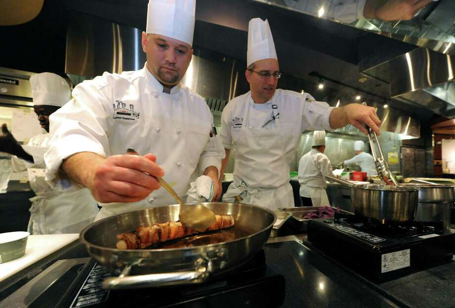 Sous chef Justin Lizotte, left, and executive sous chef Toby Hewitt of the Tufts University team, compete in the 2nd annual culinary conference and competition at Skidmore College Friday,  Jan. 11, 2013, in Saratoga Springs, N.Y. (Michael P. Farrell/Times Union) Photo: Michael P. Farrell