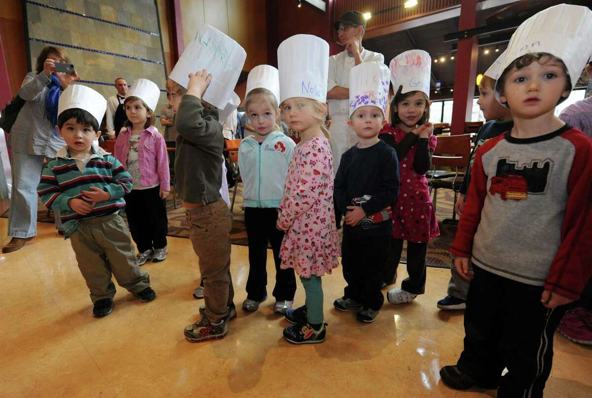 Dressed in chef hats children from the Skidmore College Greenberg Childcare Center watch chefs plate dinners during the 2nd annual culinary conference and competition at Skidmore College Friday, Jan. 11, 2013, in Saratoga Springs, N.Y. (Michael P. Farrell/Times Union)