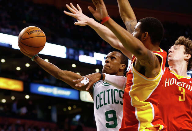 Celtics point guard Rajon Rondo attempts a shot over Rockets center Omer Asik. Photo: Jared Wickerham / 2013 Getty Images