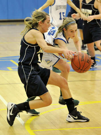 Newtown's Sarah Lynch gets a hand on the ball of Michelle DeSantis, of Lauralton Hall, during their game at Newtown High School on Friday, Jan. 11, 2013. Lauralton Hall won, 50-44. Photo: Jason Rearick / The News-Times