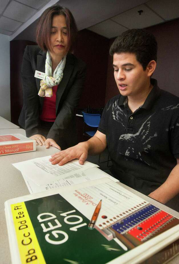 Po Chu Leung, testing director at UH-Downtown, goes over the new GED curriculum with student worker Juan Lopez. The test is revised about every 10 years. Photo: J. Patric Schneider, Freelance / © 2013 Houston Chronicle