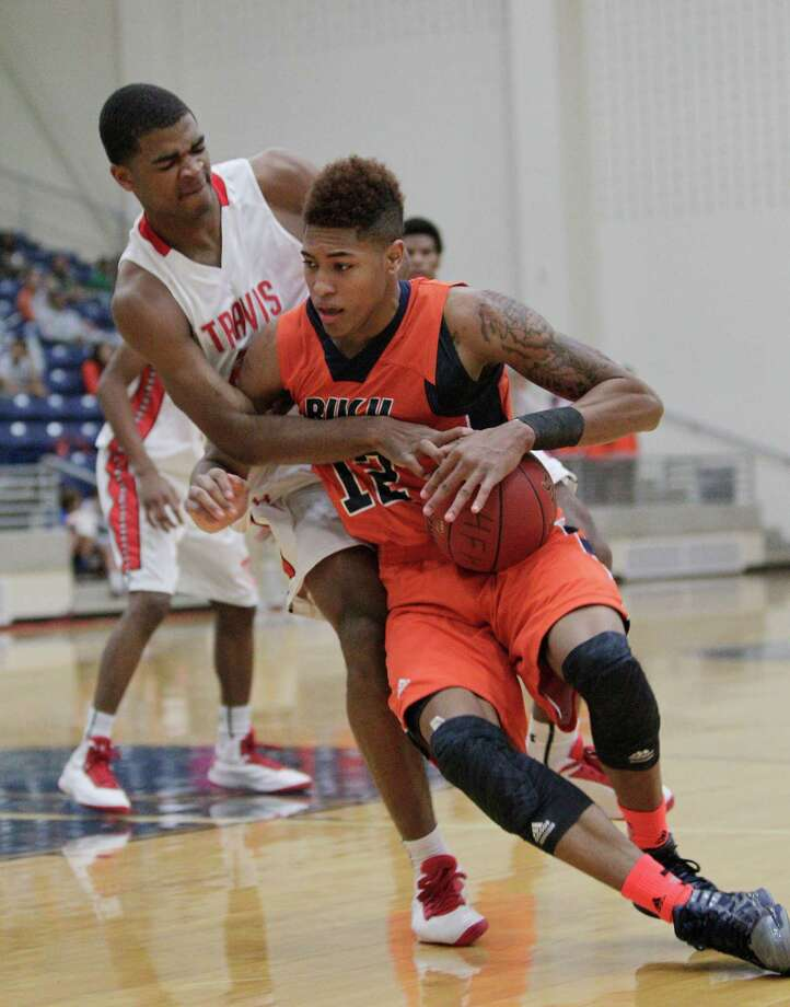 Bush's Kelly Oubre drives around Travis' Aaron Harrison during a high school basketball game between Travis and Bush at Hopson Fieldhouse, Friday, January 11, 2013. Bush defeated Travis 61-58 in overtime. Photo: Bob Levey, Houston Chronicle / ©2013 Bob Levey