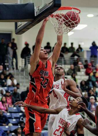 Bush's Jalin Le Blanc dunks over Travis' Daniel Chika and Tyronne Jordan, bottom, during a high school basketball game between Travis and Bush at Hopson Fieldhouse, Friday, January 11, 2013. Bush defeated Travis 61-58 in overtime. Photo: Bob Levey, Houston Chronicle / ©2013 Bob Levey