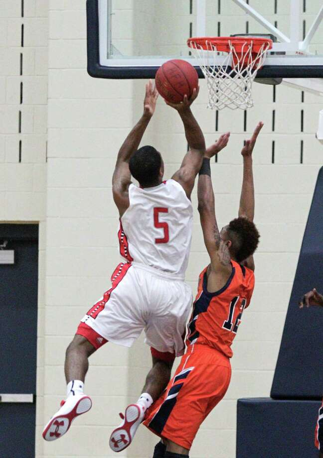 Travis' Andrew Harrison drives to the basket over Travis' Kelly Oubre during a high school basketball game between Travis and Bush at Hopson Fieldhouse, Friday, January 11, 2013. Bush defeated Travis 61-58 in overtime. Photo: Bob Levey, Houston Chronicle / ©2013 Bob Levey