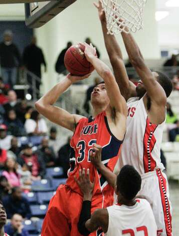 Bush's Jalin Le Blanc drives to the basket  over the Travis defense during a high school basketball game between Travis and Bush at Hopson Fieldhouse, Friday, January 11, 2013. Bush defeated Travis 61-58 in overtime. Photo: Bob Levey, Houston Chronicle / ©2013 Bob Levey