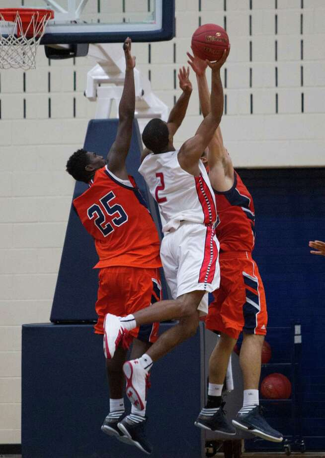 Travis' Aaron Harrison goes up over Bush's Brandon Jones #25 for a layup attempt during a high school basketball game between Travis and Bush at Hopson Fieldhouse, Friday, January 11, 2013. Bush defeated Travis 61-58 in overtime. Photo: Bob Levey, Houston Chronicle / ©2013 Bob Levey