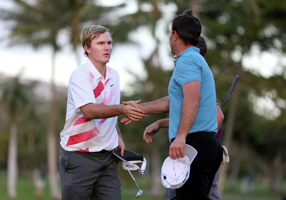 HONOLULU, HI - JANUARY 10:  Russell Henley (L) shakes hands with Luke Guthrie on the 18th hole green after completing the first round of the Sony Open in Hawaii at Waialae Country Club on January 10, 2013 in Honolulu, Hawaii.  (Photo by Christian Petersen/Getty Images) Photo: Christian Petersen, Staff / 2013 Getty Images