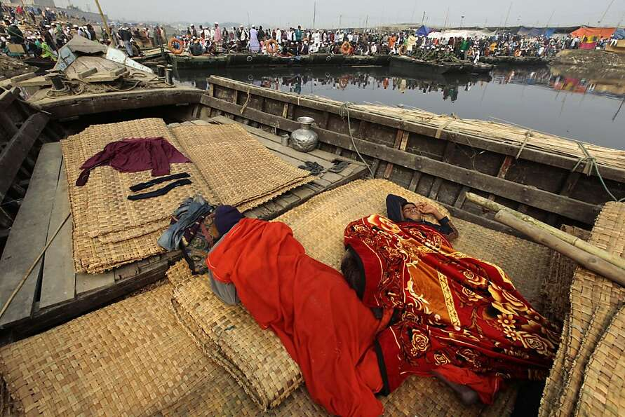Bangladeshi Muslim pilgrims take a nap on a boat as others prepare to offer prayers on the banks of