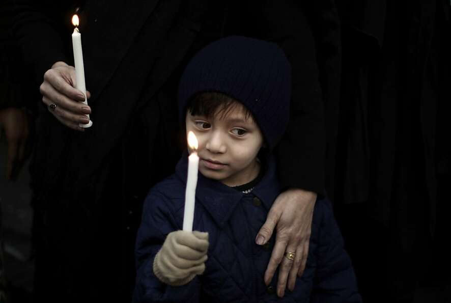 A Pakistani boy holds a candle while he and his mother take part in a protest to condemn Thursday's