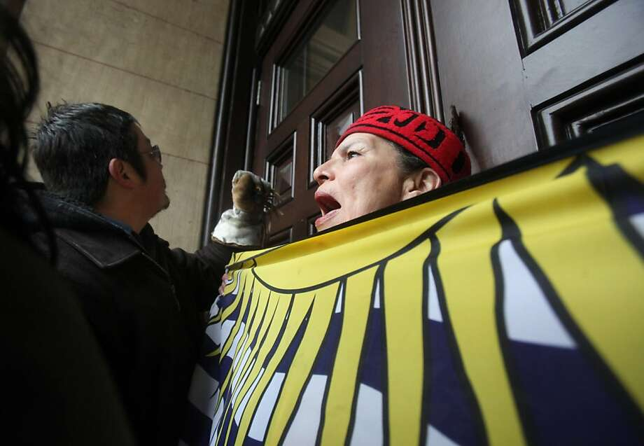 An aboriginal protestor bangs on the door to Langevin Block as Prime Minister Steven Harper meets inside with native leaders across from Parliament Hill in Ottawa on Friday, Jan. 11, 2013.  The highly politicized meeting between Harper and First Nations leaders is underway, taking place in the prime minister's Langevin Block office despite pleas that it be moved. About 20 First Nations leaders attended the meeting, representing most areas of the country, even after a tumultuous night of talks that saw chief after chief reject the meeting because it was not on their turf or on their terms. Photo: Patrick Doyle, Associated Press