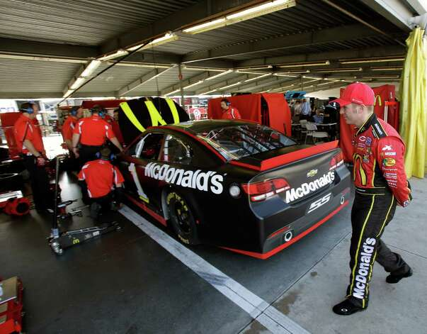 Jamie McMurray, right, watches as crew members make adjustments to his car in his garage during NASCAR auto race testing at Daytona International Speedway, Friday, Jan. 11, 2013, in Daytona Beach, Fla. (AP Photo/John Raoux) Photo: John Raoux