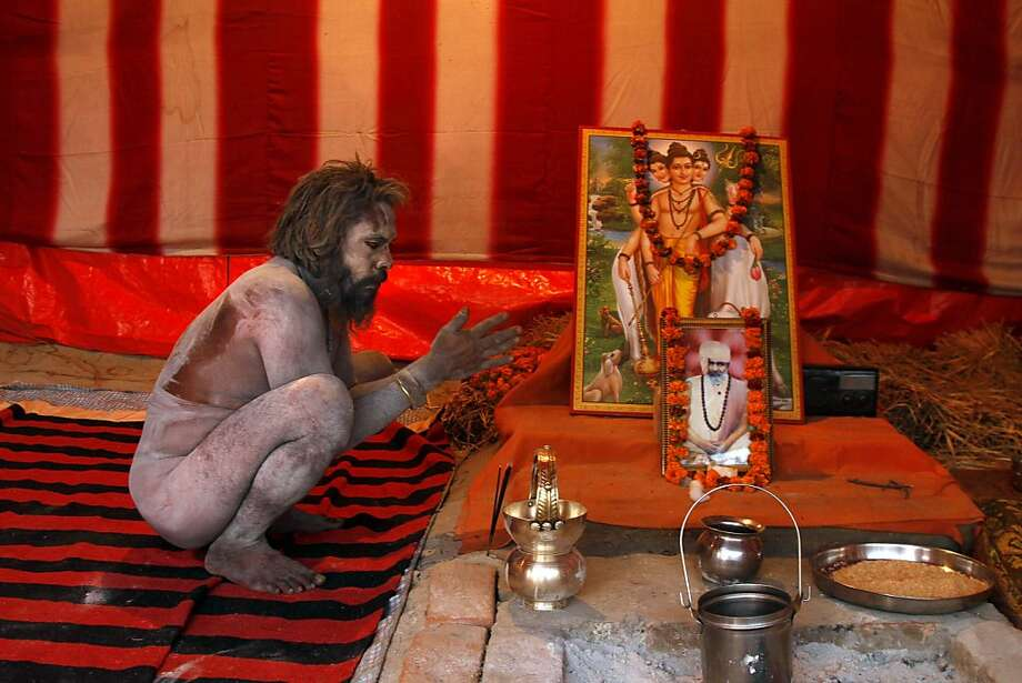 A Naga sadhu, or naked Hindu holy man, prays inside his camp at the Sangam, the confluence of rivers Ganges, Yamuna and mythical Saraswati, in Allahabad, india, Friday, Jan. 11, 2013. Millions of Hindu pilgrims are expected to take part in the Maha Kumbh festival, a large religious congregation of a period of over a month, which falls every 12th year. Photo: Rajesh Kumar Singh, Associated Press