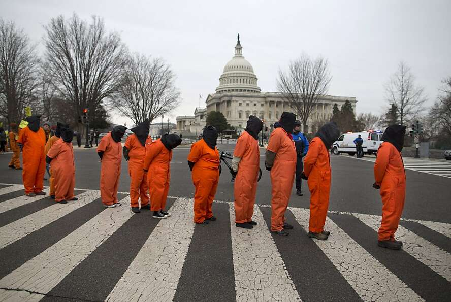Demonstrators, dressed as detainees, march past the Capitol building on Capitol Hill in Washington,