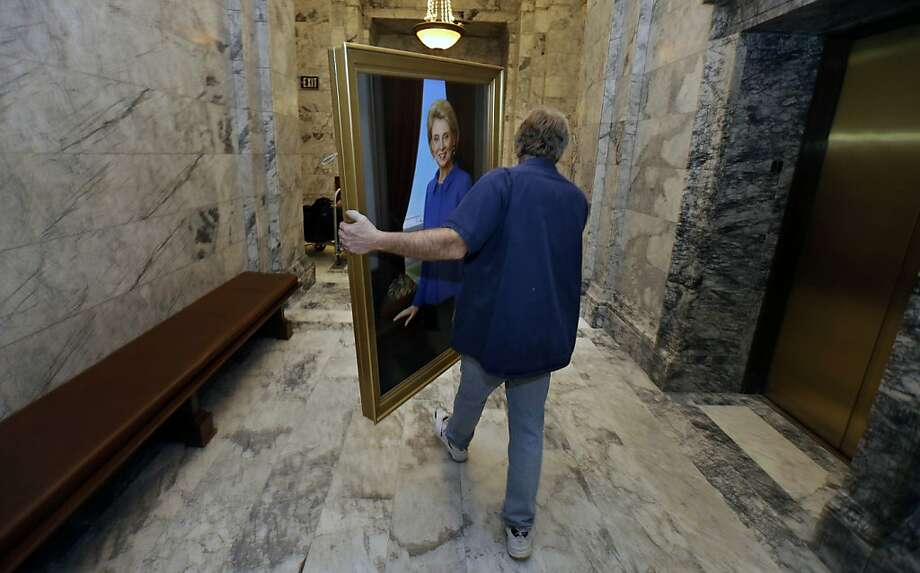 Jim Buenzli, of the Dept. of Enterprise Services, carries the official portrait of Washington Gov. Chris Gregoire, through a hallway at the Capitol after it was unveiled, Friday, Jan. 11, 2013, in Olympia, Wash. The painting, which was done by Sammamish, Wash. artist Michele Rushworth, left, will hang alongside other former governors in the Governor's office. Gregoire, who has served two terms as Governor, will be leaving office Wednesday, Jan. 16, 2013 when Gov.-elect Jay Inslee is sworn in. Photo: Ted S. Warren, Associated Press