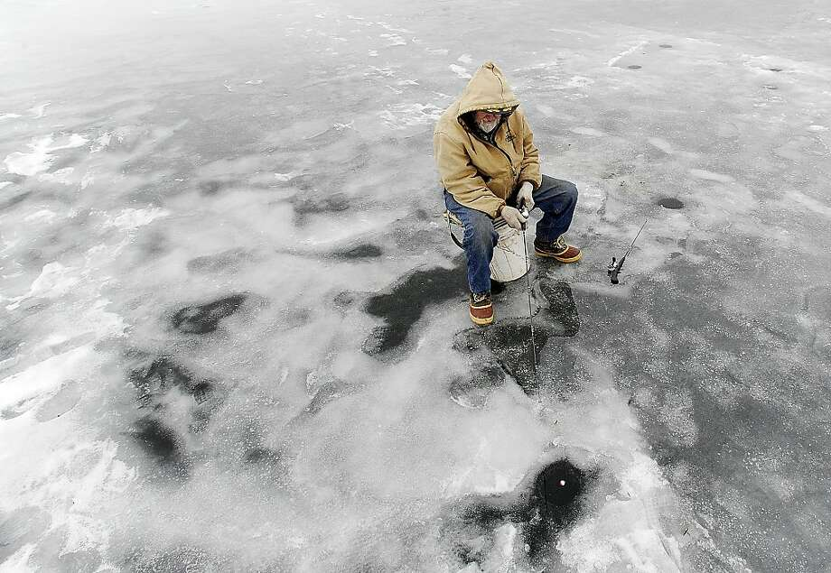 "Tony Bambenek of Bluff Siding, Wis., fishes Friday, Jan. 11, 2013, on East Lake Winona in Winona, Minn. Despite the 40-degree temperature, ice on the lake remains around 10 inches. ""I like this weather,"" Bambenek said. ""It's better than 20 below. I wouldn't be out her if it was that cold.""  Photo: Andrew Link, Associated Press"