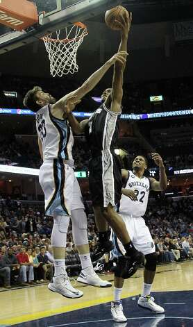 Spurs forward Kawhi Leonard (2) goes to the basket and is fouled by Grizzlies center Marc Gasol (33) with Grizzlies forward Rudy Gay (22) watching in the first half  on Friday, Jan. 11, 2013, in Memphis, Tenn. Photo: Lance Murphey, Associated Press / FR78211 AP