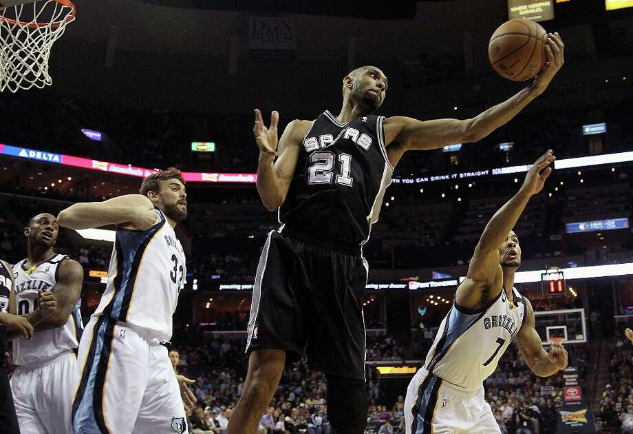 Spurs forward Tim Duncan (21) grabs a rebound against Grizzlies defenders Darrell Arthur (00), Marc Gasol (33)  and Jerryd Bayless (7) in the first half  on Friday, Jan. 11, 2013, in Memphis, Tenn. Photo: Lance Murphey, Associated Press / FR78211 AP