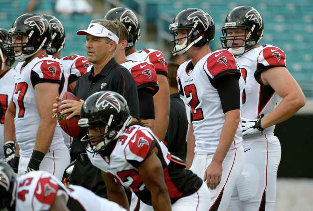 FILE - This Aug. 30, 2012 file photo shows Atlanta Falcons quarterback Matt Ryan (2) and offensive coordinator Dirk Koetter, second from left, watching the team perform drills prior to a preseason NFL football game against the Jacksonville Jaguars in Jacksonville, Fla. In their first year with the Atlanta Falcons, defensive coordinator Mike Nolan and offensive coordinator Koetter helped energize the entire roster by putting star players in position to succeed and by giving all the reserves a chance to contribute. The formula has worked thus far, but Nolan and Koetter know their entire body of work this season will be judged on how well Atlanta performs in the playoffs. (AP Photo/Phelan M. Ebenhack, File) Photo: Phelan M. Ebenhack, FRE / FR121174 AP
