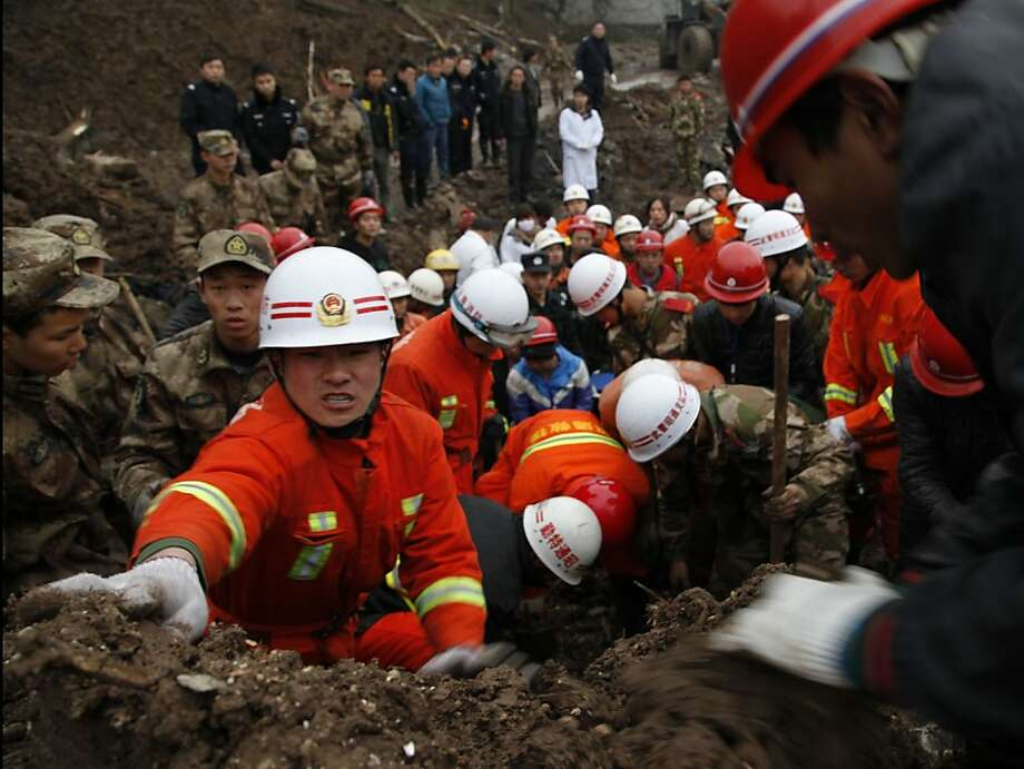 In this Jan. 11, 2013 photo provided by China's Xinhua News Agency, rescuers work at the mud-inundated debris after a landslide hit Zhaojiagou in Zhenxiong County, southwest China's Yunnan Province. A landslide swept through the village in the steep, snow-dusted mountains of southern China on Friday, killing at least 32 people, the local government said. Photo: Zhuang Gangyu, Associated Press