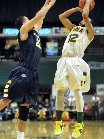 Siena's Rakeem Brookins (12), right, shoots for three points as Canisius' Isaac Sosa (22) defends during their basketball game on Friday, Jan. 11, 2013, at Times Union Center in Albany, N.Y. Brookins hits the basket to win 57-54 in the final second. (Cindy Schultz / Times Union) Photo: Cindy Schultz / 00020599C