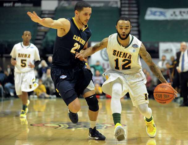 Siena's Rakeem Brookins (12), right, drives up court as Canisius' Isaac Sosa (22) defends during their basketball game on Friday, Jan. 11, 2013, at Times Union Center in Albany, N.Y. Brookins hits a 3-point basket to win 57-54 in the final second. (Cindy Schultz / Times Union) Photo: Cindy Schultz / 00020599C