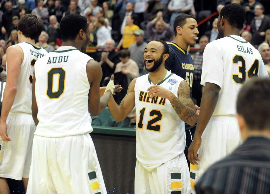 Siena's Rakeem Brookins (12), center, celebrates their win over Canisius in their conference basketball game on Friday, Jan. 11, 2013, at Times Union Center in Albany, N.Y. Brookins hits a 3-point basket to win 57-54 in the final second. (Cindy Schultz / Times Union) Photo: Cindy Schultz / 00020599C