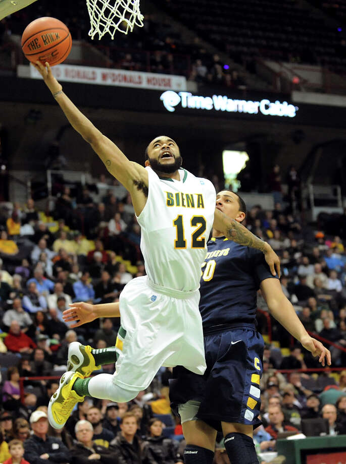 Siena's Rakeem Brookins (12), left, shoots for the hoop as Canisius' Josiah Heath (50) defends during their basketball game on Friday, Jan. 11, 2013, at Times Union Center in Albany, N.Y. (Cindy Schultz / Times Union) Photo: Cindy Schultz / 00020599C