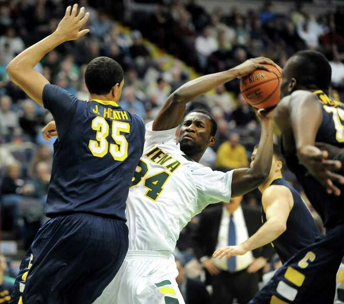 Siena's Imoh Silas (34), center, protects the ball as Canisius' Jordan Heath (35) applies pressure d