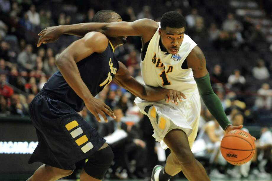 Siena's O.D. Anosike (1), right, drives past Canisius' Chris Manhertz (13) during their basketball game on Friday, Jan. 11, 2013, at Times Union Center in Albany, N.Y. (Cindy Schultz / Times Union) Photo: Cindy Schultz / 00020599C