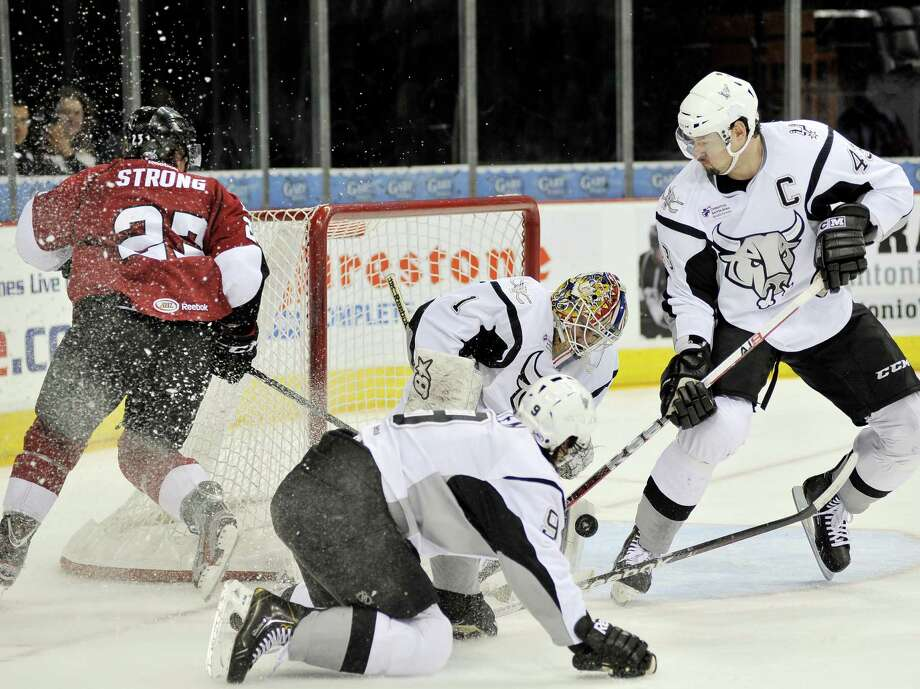 San Antonio Rampage goaltender Dov Grumet-Morris makes a save on Lake Erie Monsters' Dean Strong, left rear, with help from San Antonio's Nolan Yonkman, right, and Jonathan Hazen, front, during the first period of an AHL hockey game, Friday, Jan. 11, 2013, in San Antonio. (Darren Abate/pressphotointl.com) Photo: Darren Abate, For The Express-News / Darren Abate/pressphotointl.com