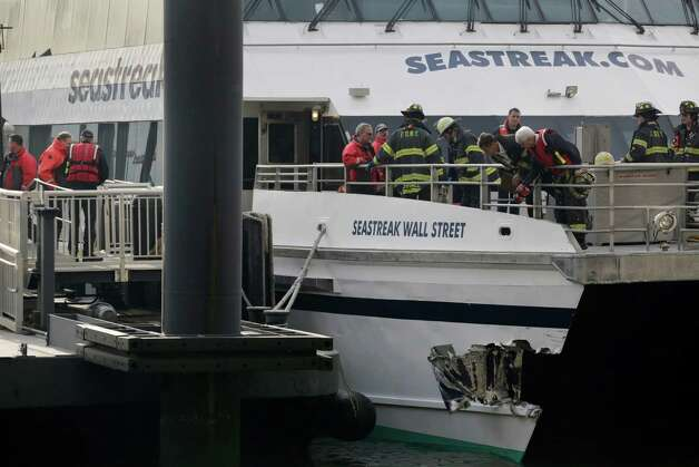 New York City firefighters walk the deck of the Seastreak Wall Street ferry in New York on  Wednesday. The ferry from Atlantic Highlands, N.J., banged into the mooring as it arrived at South Street in lower Manhattan during morning rush hour, injuring as many as 50 people, at least one critically, officials said. Photo: AP