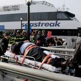 An injured passenger from the Seastreak Wall Street ferry is taken to an ambulance, in New York on Wednesday. The ferry from Atlantic Highlands, N.J., banged into the mooring as it arrived at South Street in lower Manhattan during morning rush hour, injuring as many as 50 people, at least one critically, officials said.