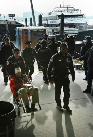 Paramedics wheel an injured ferry passenger away after the boat crashed on Wednesday in New York.  At least 57 people were injured, two critically, when a commuter ferry struck a dock in New York City's financial district, ripping open a right-side front corner. Photo: AP