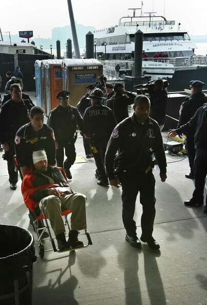 Paramedics wheel an injured ferry passenger away after the boat crashed on Wednesday in New York.  A